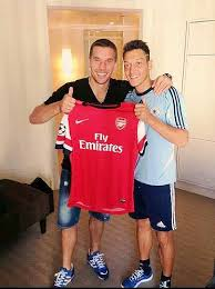 Mesut Ozil sporting his new kit with German teammate Lukas Podolski